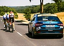 Tour de France 2020 - Foto ciclistas em rodovia sendo acompanhados por carro de suporte.