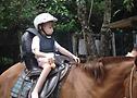 (criança passeando em cavalo com sela adaptada)