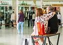 (imagem de casal sentado em um banco em uma praça de compras)